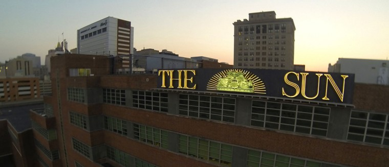 The Baltimore Sun building's neon sign is pictured on Guilford Street at sunset. (Jerry Jackson/Baltimore Sun)