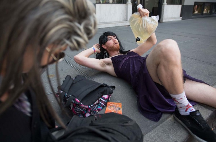 A man who only gave his name as Yolanda (right) drinks wine out of a plastic bag during the 18th annual How Weird Street Faire in San Francisco, California on May 07, 2017. Several city blocks filled with thousands of people as they partied and danced in costume to electronic music and interacted with street performers and artists. (JOSH EDELSON/AFP/Getty Images)