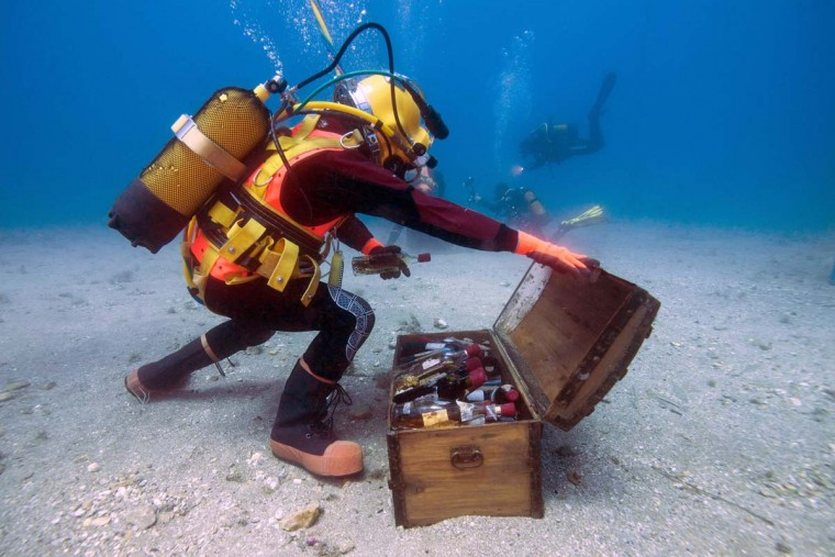 A diver takes wine bottles from an underwater trunk in the Mediterranean Sea off Saint-Mandrier, southern France on May 15, 2017. Bandol wine matured underseas before being analyzed after one year. (BORIS HORVAT/AFP/Getty Images)