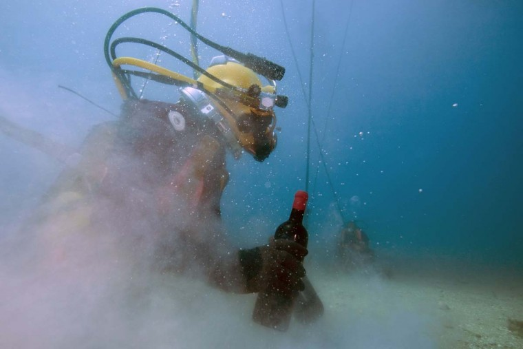 A diver holds a bottle of wine taken from an underwater wine cellar in the Mediterranean Sea off Saint-Mandrier, southern France on May 15, 2017. Bandol wine matured underseas before being analyzed after one year. (BORIS HORVAT/AFP/Getty Images)