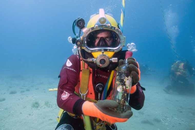 A diver shows a bottle from an underwater wine cellar in the Mediterranean sea off Saint-Mandrier, southern France on May 15, 2017. Bandol wine matured underseas before being analyzed after one year. (BORIS HORVAT/AFP/Getty Images)