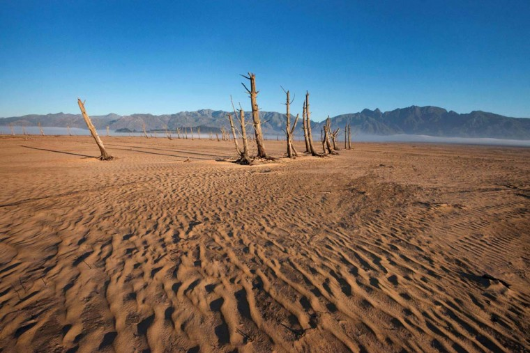 A picture taken on May 10, 2017 shows bare sand and dried tree trunks standing out at Theewaterskloof Dam, which has less than 20% of it's water capacity, near Villiersdorp, about 108km from Cape Town. This dam is the main water source for the city of Cape Town, and there is only 10% of it's usual capacity left for human consumption, at the last 10% is not usable, due to the silt content. The Western Cape Province, which includes Cape Town is suffering from one of the worst water shortages in living memory. This has necessitated the Cape Town City Council to establish stringent water usage restrictions, and unless unexpectedly heavy rains fall soon, the province will begin a cycle of drought. (RODGER BOSCH/AFP/Getty Images)