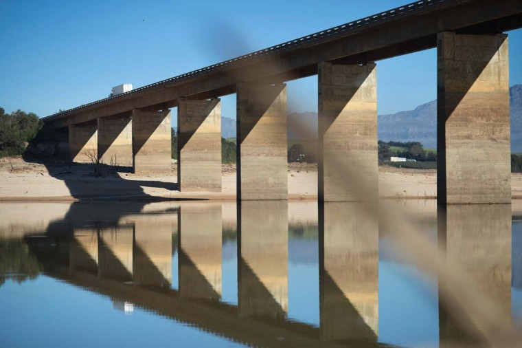 A truck crosses a bridge at Theewaterskloof Dam, which has less than 20% of it's water capacity, on May 10, 2017, near Villiersdorp, about 108Km from Cape Town, as previous high water marks are visible on the pylons. South Africa's Western Cape region which includes Cape Town declared a drought disaster on May 22 as the province battled its worst water shortages for 113 years. This dam is the main water source for the city of Cape Town, and there is only 10% of it's usual capacity left for human consumption, at the last 10% is not usable, due to the silt content. (RODGER BOSCH/AFP/Getty Images)