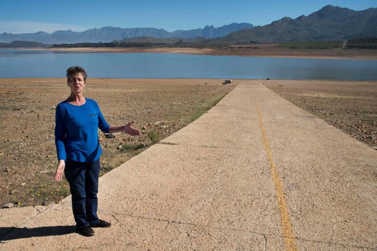 Lisa Wheeler, secretary of the Theewaterskloof Sports Club, shows where the high water mark of the dam is, which has less than 20% of it's water capacity, on May 10, 2017, near Villiersdorp, about 108Km from Cape Town. South Africa's Western Cape region which includes Cape Town declared a drought disaster on May 22 as the province battled its worst water shortages for 113 years. This dam is the main water source for the city of Cape Town, and there is only 10% of it's usual capacity left for human consumption, at the last 10% is not usable, due to the silt content. (RODGER BOSCH/AFP/Getty Images)