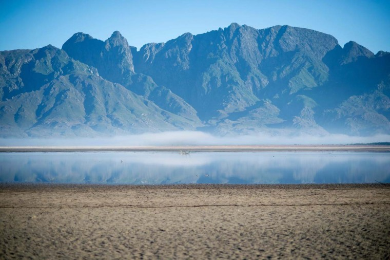 A picture taken on May 10, 2017 shows bare sand and a narrow body of water facing the sky at Theewaterskloof Dam, which has less than 20% of it's water capacity, near Villiersdorp, about 108Km from Cape Town. South Africa's Western Cape region which includes Cape Town declared a drought disaster on May 22 as the province battled its worst water shortages for 113 years. This dam is the main water source for the city of Cape Town, and there is only 10% of it's usual capacity left for human consumption, at the last 10% is not usable, due to the silt content. (RODGER BOSCH/AFP/Getty Images)
