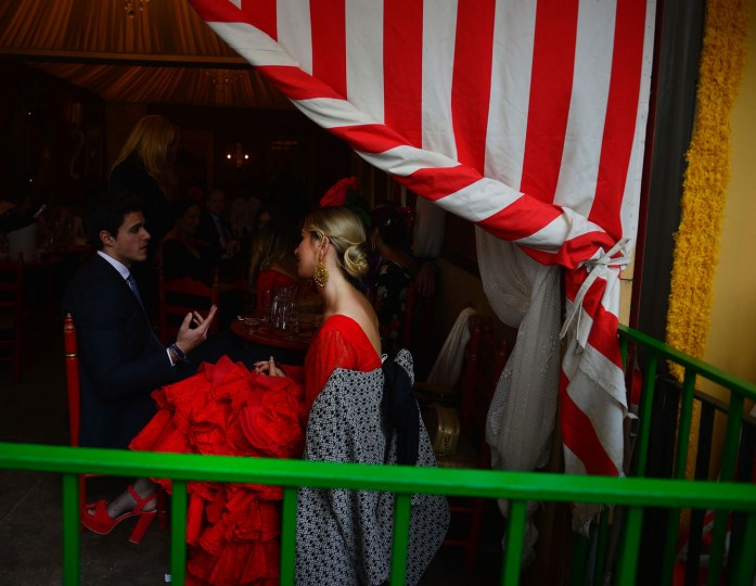 "A woman wearing a traditional Sevillian dress speaks with a man inside a booth during the ""Feria de Abril"" (April Fair) in Sevilla on April 30, 2017. The fair dates back to 1847 when it was originally organized as a livestock fair but has turned into a week of flamenco dancing, music and bullfighting. (Cristina Quicler/AFP/Getty Images)"
