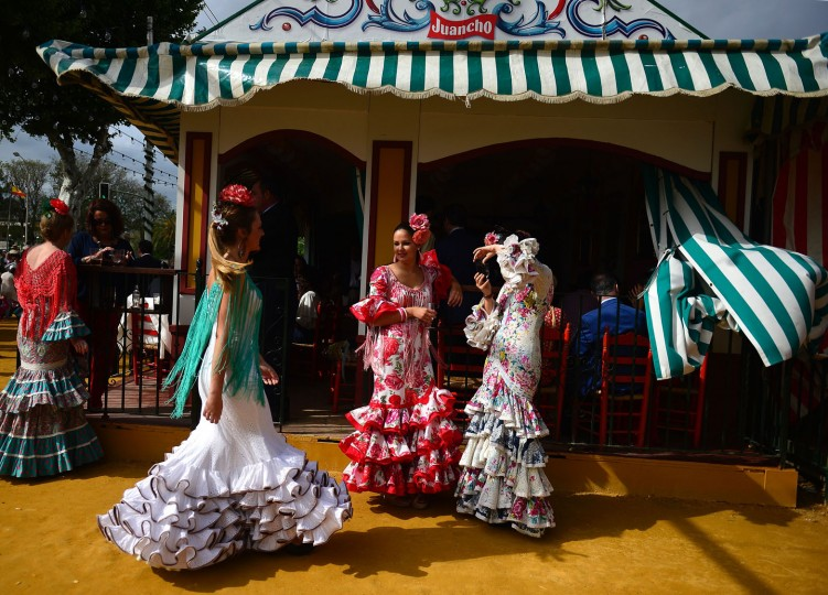 "A woman wearing a traditional Sevillian dress poses for a picture during the ""Feria de Abril"" (April Fair) in Sevilla on April 30, 2017. The fair dates back to 1847 when it was originally organized as a livestock fair but has turned into a week of flamenco dancing, music and bullfighting. (Cristina Quicler/AFP/Getty Images)"