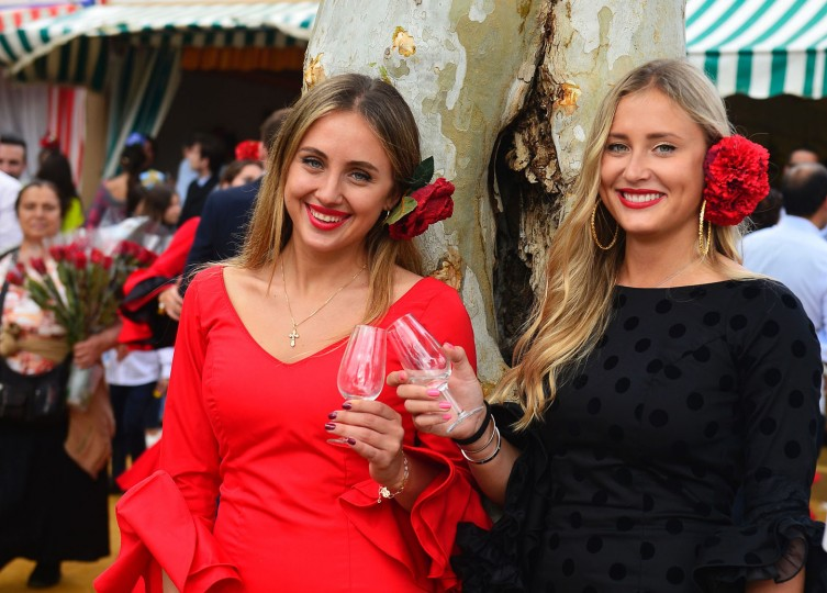 "Two women wearing traditional Sevillian dresses drink a toast as they pose during the ""Feria de Abril"" (April Fair) in Sevilla on April 30, 2017. The fair dates back to 1847 when it was originally organized as a livestock fair but has turned into a week of flamenco dancing, music and bullfighting. (Cristina Quicler/AFP/Getty Images)"