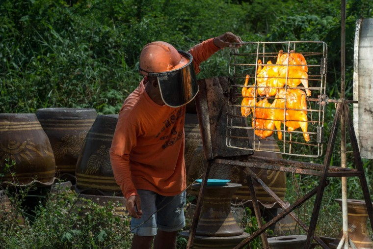 This picture taken on May 4, 2017 shows food vendor Sila Sutharat looking at chicken being cooked by rays of sun reflected onto an oversized mirror panel on his property in Petchaburi province, south of Bangkok. Not many chefs don a welding mask before they enter the kitchen, but Sila Sutharat prefers to cook his chicken sunny side up. Two hours south of Bangkok this 60-year-old vendor has found an ingenious way to offer his customers something a little different by harnessing the power of the sun. Using a large wall of nearly 1,000 moveable mirrors -- a device he designed and built himself -- he focuses the sun's rays onto a row of marinated chickens, sizzling away under the intense heat. (ROBERTO SCHMIDT/AFP/Getty Images)