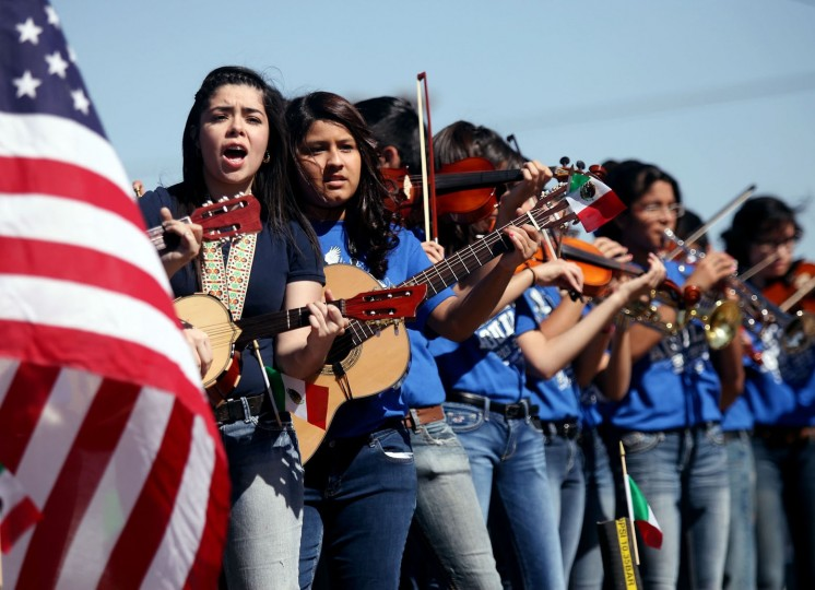 FILE--In this May 3, 2014, file photo, members of the Ector Junior High Mariachi Band perform while riding on a float during the Cinco de Mayo parade on Crane Avenue in Odessa, Texas. Trump's immigration policies and rhetoric are leaving some Mexican Americans and immigrants feeling at odds with a day they already thought was appropriated by beer and liquor companies, event promoters and local bars. (Edyta Blaszczyk/Odessa American via AP, file)