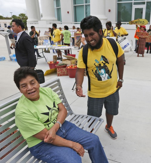 In this Monday, May 1, 2017 photo, Jose Luis Santiago, right, an immigration advocate, chats with a demonstrator before a protest march in Homestead, Fla. President Donald Trump's immigration policies and rhetoric are leaving some Mexican Americans and immigrants feeling at odds with Cinco de Mayo. Latino activists and scholars say that ambivalence is bolstered around the hazy history of Cinco de Mayo and by the stereotypes exploited by marketers. (AP Photo/Wilfredo Lee)