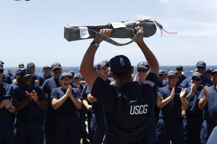 In this March 4, 2017 photo, the crew of the U.S. Coast Guard cutter Stratton cheer after a Coast Guardsman raises his lawn chair that he won during a rock-paper-scissors competition on the flight deck of the cutter while it was patrolling the eastern Pacific Ocean. The Stratton is steaming more than 500 miles south of the Guatemala-El Salvador border, considered the biggest narcotics smuggling corridor in the world. (AP Photo/Dario Lopez-Mills)