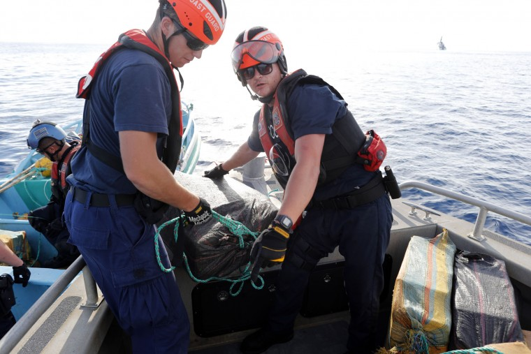In this Feb. 23, 2017 photo, a U.S. Coast Guard law enforcement team from the USCG cutter Stratton transfers bales of drugs to their boat after four men were caught on a small fishing boat carrying close to 700 kilos of pure cocaine, in the Pacific Ocean, hundreds of miles south of the Guatemala-El Salvador border. More than a dozen countries in Central and South America have essentially outsourced their drug-interdiction efforts to the U.S. (AP Photo/Dario Lopez-Mills)