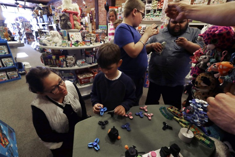 In this Thursday, May 11, 2017, photo, customers look over the selection of fidget spinners at the Funky Monkey Toys store in Oxford, Mich. The fidget spinners are so popular, stores can't keep them in stock. (AP Photo/Carlos Osorio)
