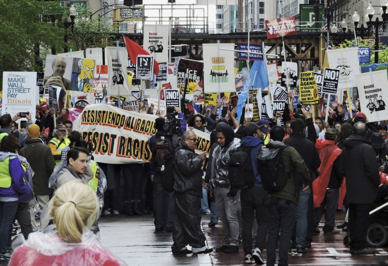 People participate in a May Day rally at the Daley Plaza in Chicago on Monday, May 1, 2017. Thousands of people from New England to the Midwest to the Southwest chanted, picketed and protested Monday as demonstrations raged against President Donald Trump's immigration policies along with the traditional May Day marching in favor of labor. (Brian Jackson/Chicago Sun-Times via AP)
