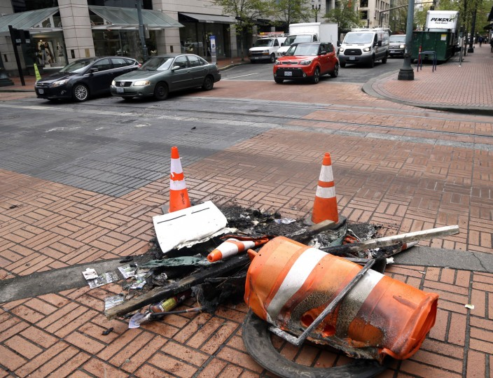 Charred and melted debris is still visible on a downtown street corner the day after a May Day march in Portland, Ore., Tuesday, May 2, 2017. May Day protests turned violent in the Pacific Northwest as demonstrators in Portland threw smoke bombs and other objects at police, setting fires in the street while elsewhere thousands of people peacefully marched against President Donald Trump's immigration and labor policies. (AP Photo/Don Ryan)