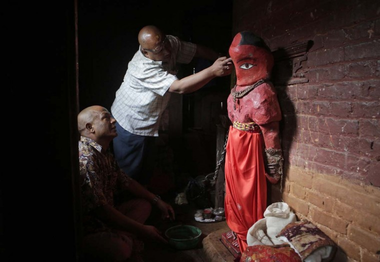In this April 19, 2017, photo, Chitrakar artist Amir Nekhu helps repair the statue of Rato Machindranath in Machindra Bahal in Lalitpur, Nepal. The wide-eyed, red painted clay statue of Machindranath is kept locked away for months until it is to be carried in a chariot for the Rato Machindranath festival. For generations now, men have worked for weeks every spring season to build the chariot for the annual harvest festival. (AP Photo/Niranjan Shrestha)