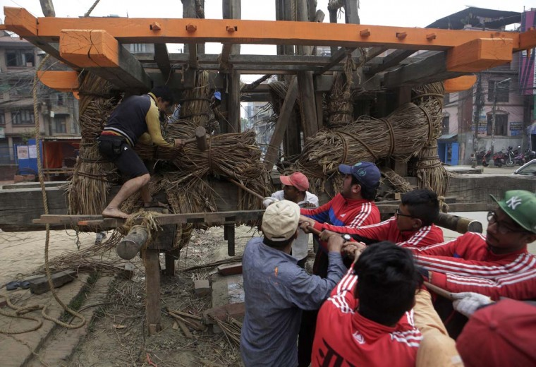 In this April 19, 2017, photo, members of the Yanwal community tie bundles of cane together in the construction of the Rato Machindranath Chariot in Lalitpur, Nepal. The wooden chariot is built to appease the gods in hopes of being blessed with good rainfall followed by a bountiful harvest. The chariot built every year is 15-meter (48-foot) tall and based on a chassis that is only wide as a small truck. The Yanwals have the task of tying the tower of logs together with trucks loads of cane. (AP Photo/Niranjan Shrestha)