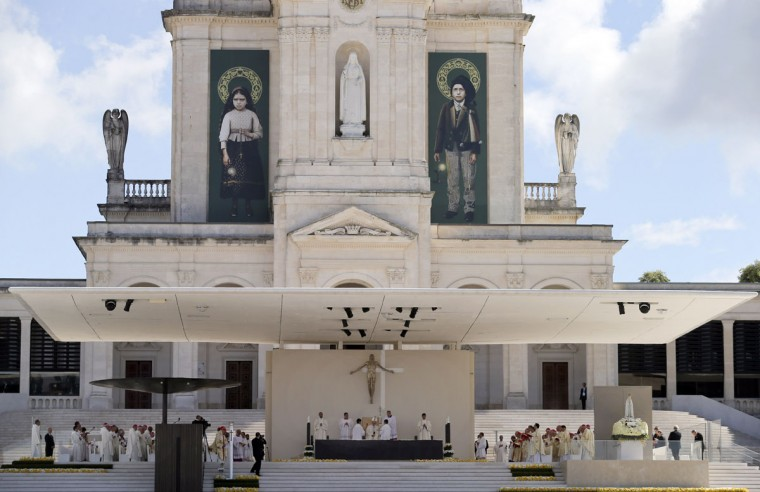 The pictures of Jacinta, left, and Francisco Marto, hang on the facade of the Sanctuary of Our Lady of Fatima in Fatima, Portugal. (AP Photo/Armando Franca)