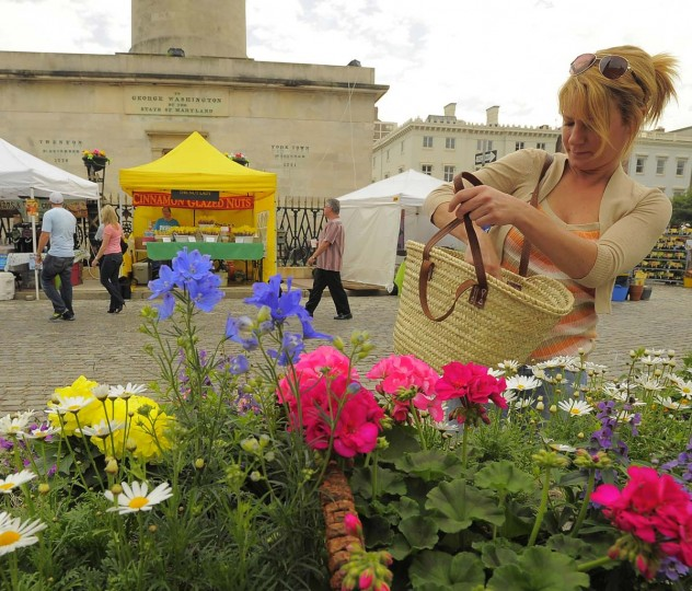 Zorana Grdjic of Fells Point makes a purchase at Baltimore's FlowerMart 2012 at Mount Vernon, at the base of the Washington Monument on Charles Street on May 4, 2012. (Karl Merton Ferron / Baltimore Sun Staff)