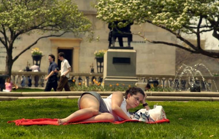 Cara Ogren of Mount Vernon takes advantage of the day, relaxing while reading a book at Mount Vernon Square on April 18, 2004. (Baltimore Sun/Karl Merton Ferron)