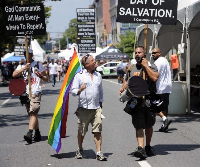 Carrying a rainbow flag, Eric Martin of Mount Vernon follows Ron Christian of Las Vegas, with the All Grace Church. Martin was following Christian around as Christian used a bullhorn to protest during the Baltimore Pride 2016 activities on July 23, 2016. (Kim Hairston/Baltimore Sun)