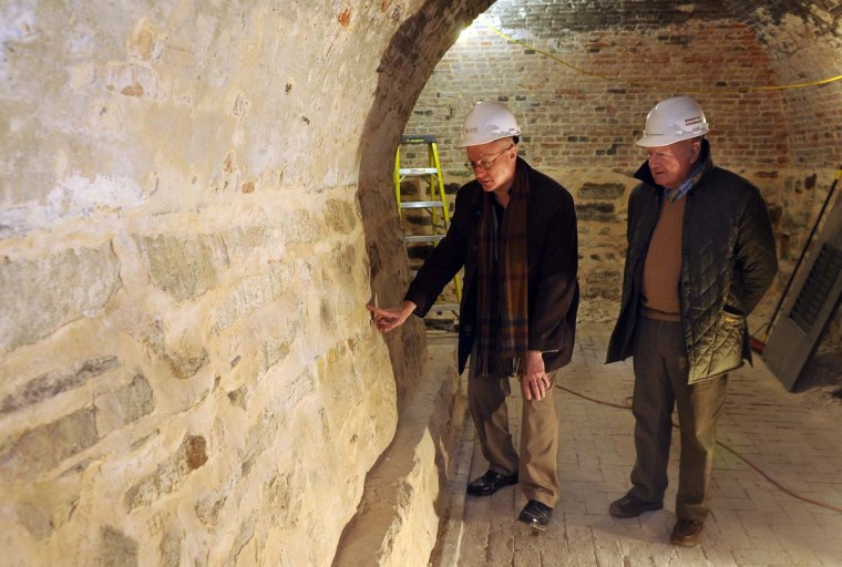 Dr. Lance Humphries, left, chairman of the Mt. Vernon Place Conservancy, looks at a wall inside the Washington Monument with Fred Eisenbrandt, right, a historic building restoration contractor. Signatures dating from the 1800s were found on walls inside the base of the Washington Monument. The signatures and drawings could have been done by the original workers at the site. Feb. 7, 2014 (Barbara Haddock Taylor/Baltimore Sun)
