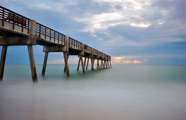 "Greg Wareheim used a Nikon D3000, a 3.0 neutral density filter and a 94-second exposure to photograph this Vero Beach, Florida pier. The 3.0 density filter darkens the image and allows for a slower shutter speed. Baltimore Sun photographer Algerina Perna comments, ""The long exposure mutes the tones of the sand and water to create this captivating and ethereal image. Wareheim took this photograph to another level by not only photographing what was before him, but interpreting it through the exposure and filter, and in the process, created art."""