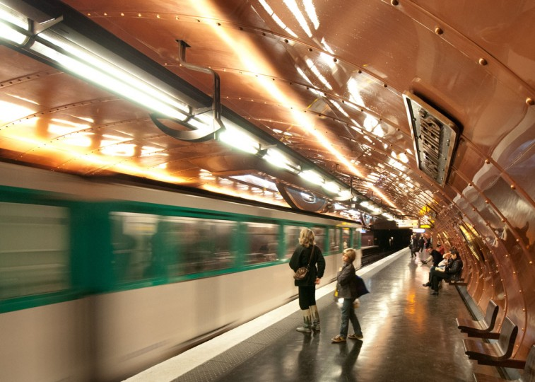 "Zoltan Levay captured this shot of people waiting for a train at the Paris Metro. Baltimore Sun photographer Algerina Perna says, ""The slow shutter speed which captures the motion of the train and people in the foreground gives energy to the photo. The camera angle emphasizes the arched ceiling covering the train on its forward path."""