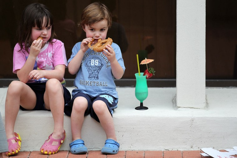 Staff Photo by Jen Rynda Mason Rickey, 5, of Cedarcroft neighborhood munches on a soft pretzel with her brother Max, right, 4, during Towsontown Spring Festival in Towson, MD on Saturday, May 5, 2012.