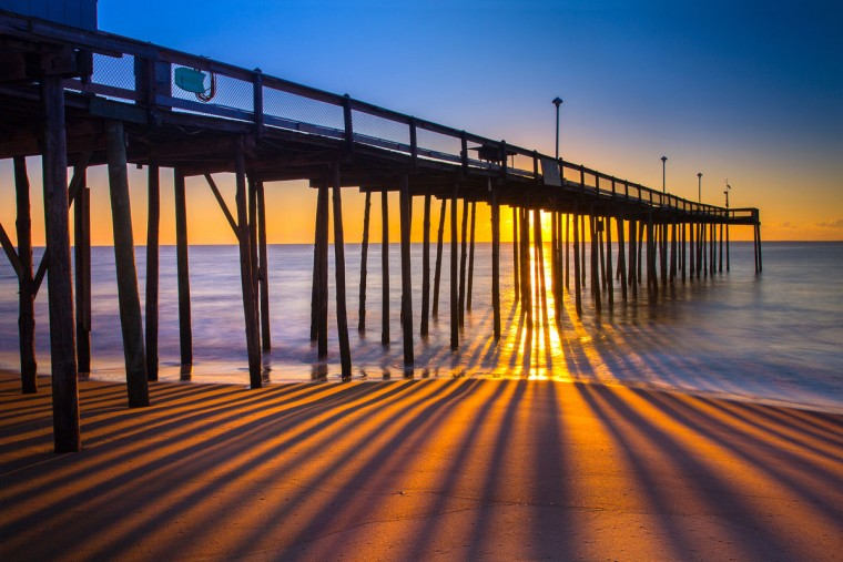 "Get imaginative with your composition. Kevin Moore took this picture of Ocean City at sunrise with a Canon 5D MKIII with a 24mm lens at f-22 and a 5 second exposure. Here is a critique by Baltimore Sun director of photography Robert Hamilton. ""You need to be a expert to know this is a gorgeous image. The photographer showed great imagination in the way he composed the image so that the sunrise streamed through the pier creating a picket fence effect with the light."""