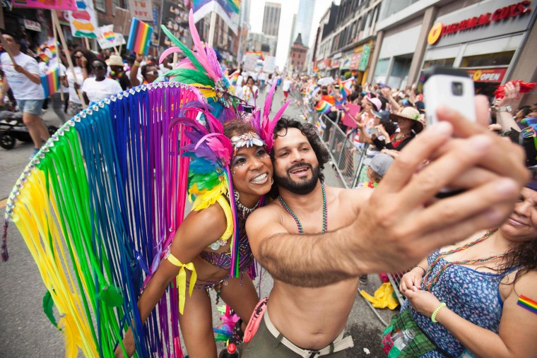 A man takes a selfie with a costumed dancer during the Pride Parade in Toronto, Ontario, June 25, 2017. (Geoff Robins/AFP/Getty Images)
