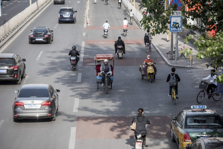 This photo taken on April 22, 2017 shows a rickshaw driver (C) riding down a busy street in Beijing. Appearing in China at the end of the 19th century, rickshaws originally had two wheels and were pulled by their driver on foot, with passengers seated at the back. Today, most of the vehicles are tricycles - some still have pedals and are propelled by physical force, but the majority are equipped with electric or gas engines. (FRED DUFOUR/AFP/Getty Images)