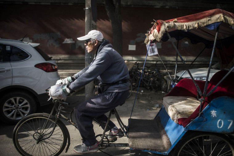 This photo taken on April 22, 2017 shows a rickshaw driver riding down a street in Beijing. Appearing in China at the end of the 19th century, rickshaws originally had two wheels and were pulled by their driver on foot, with passengers seated at the back. Today, most of the vehicles are tricycles - some still have pedals and are propelled by physical force, but the majority are equipped with electric or gas engines. (FRED DUFOUR/AFP/Getty Images)
