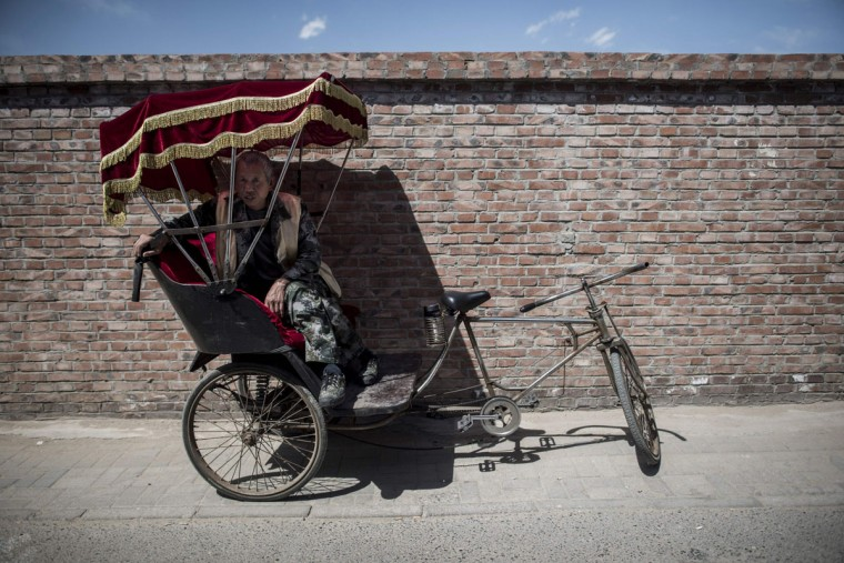 This photo taken on April 23, 2017 shows a rickshaw driver waiting for customers in Beijing. Appearing in China at the end of the 19th century, rickshaws originally had two wheels and were pulled by their driver on foot, with passengers seated at the back. Today, most of the vehicles are tricycles - some still have pedals and are propelled by physical force, but the majority are equipped with electric or gas engines. (FRED DUFOUR/AFP/Getty Images)
