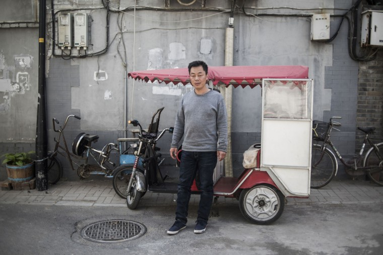 This photo taken on April 23, 2017 shows a rickshaw driver posing in Beijing. Appearing in China at the end of the 19th century, rickshaws originally had two wheels and were pulled by their driver on foot, with passengers seated at the back. Today, most of the vehicles are tricycles - some still have pedals and are propelled by physical force, but the majority are equipped with electric or gas engines. (FRED DUFOUR/AFP/Getty Images)