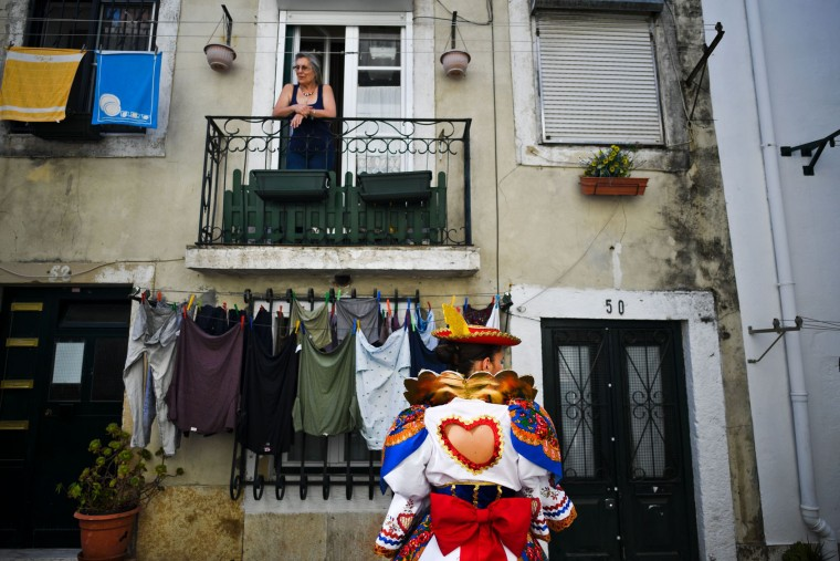 A woman stands on her balcony in the traditional Lisbon neighborhood of Alfama, as a girl dressed up in traditional costume walks past to participate in the Santo Antonio de Lisboa's Parade on Avenida da Liberdade, in Lisbon on June 12, 2017. Lisbon celebrates Saint Anthony's day, the city's protector saint, with a parade that gathers participants from several typical neighborhoods of the city. (Patricia de Melo Moreira/AFP/Getty Images)