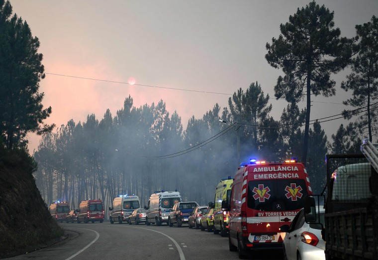 A convoy of ambulances drive during the evacuation of Picha, near Pedrogao Grande on June 20, 2017.The huge forest fire that erupted on June 17, 2017 in central Portugal killed at least 64 people and injured 135 more, with many trapped in their cars by the flames. / (AFP Photo/Francisco Leong)