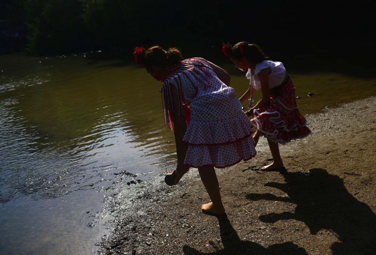 Pilgrims in traditional costume removes their shows before crossing the Quema river during the annual El Rocio pilgrimage in Villamanrique, near Sevilla on June 1, 2017. (CRISTINA QUICLER/AFP/Getty Images)