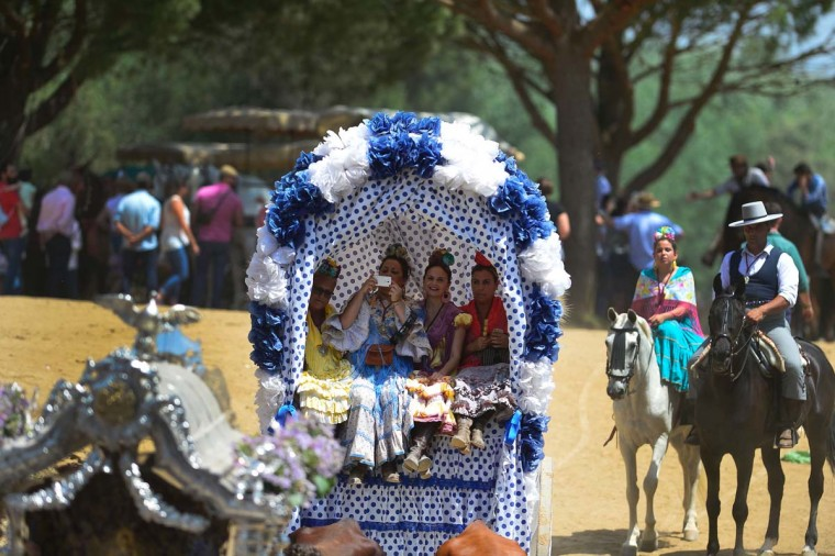Pilgrims in traditional Rocio costumes sit in a wagon as they cross the Quema river during the annual El Rocio pilgrimage in Villamanrique, near Sevilla on June 1, 2017. (CRISTINA QUICLER/AFP/Getty Images)