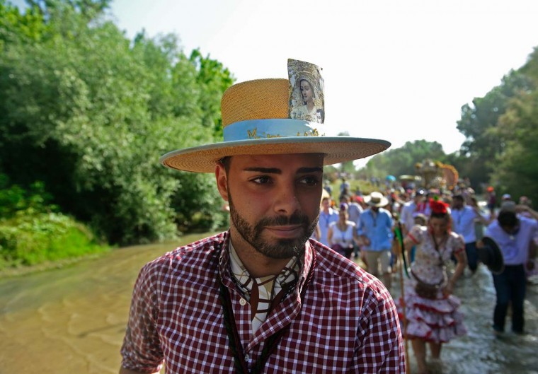 A pilgrim sporting a hat with an image of the Virgin of the Rocio crosses the Quema river during the annual El Rocio pilgrimage in Villamanrique, near Sevilla on June 1, 2017. (CRISTINA QUICLER/AFP/Getty Images)