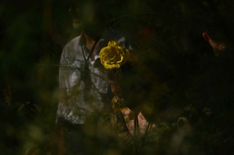 A pilgrim sporting a yellow flower in her hair is seen through vegetation near the Quema river during the annual El Rocio pilgrimage in Villamanrique, near Sevilla on June 1, 2017. (CRISTINA QUICLER/AFP/Getty Images)