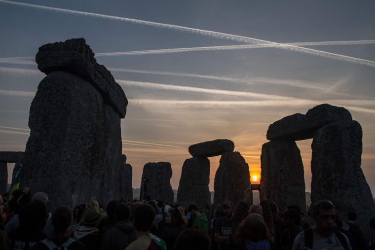 Revellers watch the sunrise as they celebrate the pagan festival of Summer Solstice at Stonehenge in Wiltshire, southern England on June 21, 2017.The festival, which dates back thousands of years, celebrates the longest day of the year when the sun is at its maximum elevation. Modern druids and people gather at the landmark Stonehenge every year to see the sun rise on the first morning of summer. / (AFP Photo/Chris Ratcliffechris j ratcliffe)