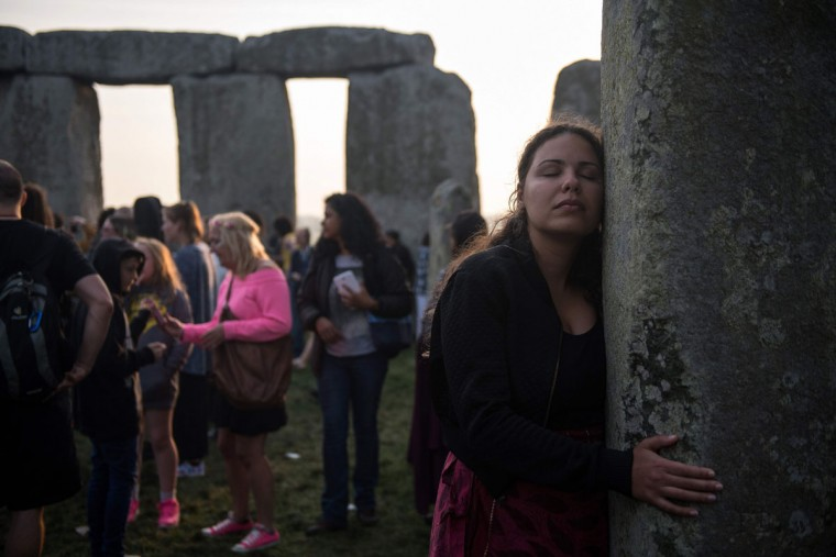 Revellers touch stones and watch the sunrise as they celebrate the pagan festival of Summer Solstice at Stonehenge in Wiltshire, southern England on June 21, 2017.The festival, which dates back thousands of years, celebrates the longest day of the year when the sun is at its maximum elevation. Modern druids and people gather at the landmark Stonehenge every year to see the sun rise on the first morning of summer. / (AFP Photo/Chris Ratcliffechris j ratcliffe)