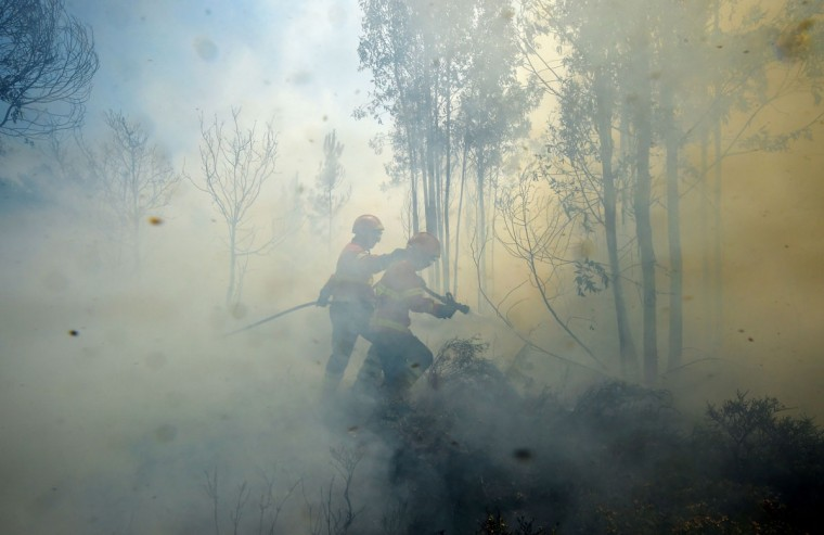 Firefighters use a hose to combat a wildfire in Vale da Ponte, Pedrograo Grande, on June 20, 2017.The huge forest fire that erupted on June 17, 2017 in central Portugal killed at least 64 people and injured 135 more, with many trapped in their cars by the flames. / (AFP Photo/Miguel Riopa)