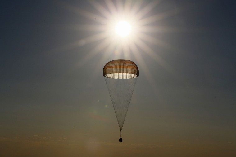 A Russian Soyuz capsule carrying two astronauts after a half-year aboard the International Space Station is silhouetted against the sun as it descends beneath a parachute before landing in a remote area outside the town of Dzhezkazgan, Kazakhstan, Friday, June 2, 2017. The capsule with the International Space Station (ISS) crew of Russian cosmonaut Oleg Novitsky and French astronaut Thomas Pesquet, landed Friday on the steppes of Kazakhstan. (Shamil Zhumatov/Pool Photo via AP)