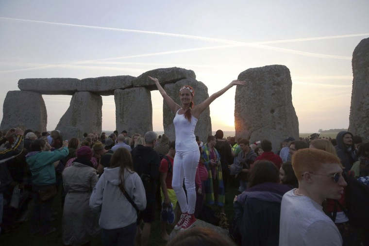 A woman stands atop an ancient stone at sunrise as some thousands gather to celebrate the Summer Solstice at Stonehenge in Salisbury, England, early Wednesday June 21, 2017. The prehistoric monument, Stonehenge is about 5000-years old and is thought to have been constructed to mark the movement of the sun and other heavenly objects according to Pagan rites. (Steve Parsons/PA via AP)