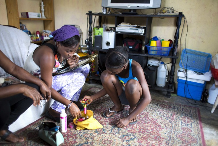 In this May 27, 2017 photo, 13-year-old Medege Dorlus helps Stephanie to look for earrings, at their home in Port-au-Prince, Haiti. Meddle is an unpaid servant and Stephanie is the daughter of the lady of the house. (AP Photo/Dieu Nalio Chery)