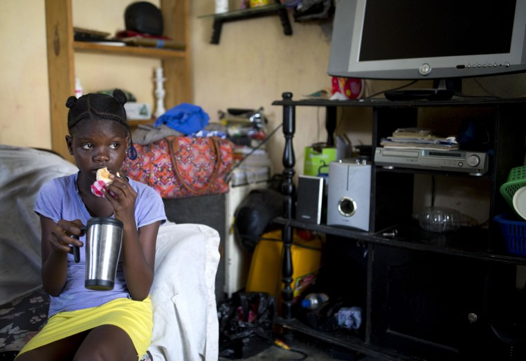 In this May 26, 2017 photo, 13-year-old Medege Dorlus eats bread with coffee at the house of a family friend that took her in after her mother died, in Port-au-Prince, Haiti. Medege had just arrived from school and was having a snack before getting to work cleaning the house. (AP Photo/Dieu Nalio Chery)
