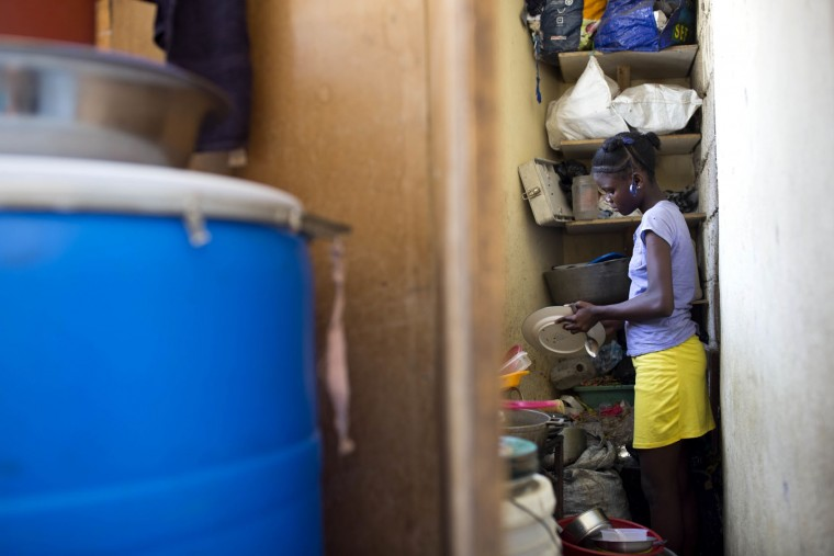 "In this May 26, 2017 photo, 13-year-old Medege Dorlus cleans dishes at the home she lives in, in Port-au-Prince, Haiti. Medege is a ""restavek,"" a term to describe children whose poor parents hand them over to others in hopes they'll have opportunities to escape a dead-end life or at least get more food. (AP Photo/Dieu Nalio Chery)"